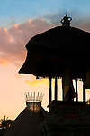 """Sunset silhouette of the crown of a Fivelements """"mandala"""" tower, alongside a traditional Balinese temple."""
