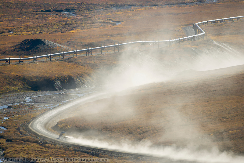 Semi tractor trailer hauls supplies along the dusty, James Dalton Highway at the base of Atigun Pass, Brooks range. Trans Alaska Oil Pipeline parallels road.