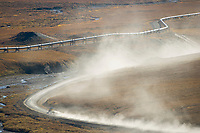 Semi tractor trailor hauls supplies along the dusty, James Dalton Highway at the base of Atigun Pass, Brooks range. Trans Alaska Oil Pipeline parallels road.