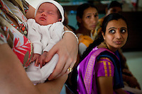 A European mother (Caroline) cradles her newborn in the Akanksha Infertility Clinic in the small town of Anand, Gujarat, India. The Akanksha Infertility Clinic is known internationally for its surrogacy program and currently has over a hundred surrogate mothers pregnant in their environmentally controlled surrogate houses. <br /> Photo by Suzanne Lee for Panos London