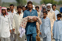 Uncle (C) is followed by other relatives, flood victims, as he carries the body of five day old Akash for his funeral in Pakistan's Muzaffargarh district of Punjab province September 6, 2010. The baby died only five days after it was born in a flooded village due to lack of medical support, family members said. Some 20 millions of Pakistani people are affected by floods that has destroyed cropland and livestock , causing damage the government has estimated at $43 billion, or almost one quarter of the South Asian nation's 2009 GDP.    REUTERS/Damir Sagolj (PAKISTAN)