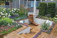 Sunken deck and steps stairs with hydrangeas in bloom, lilies, thyme herbs, Persicaria, Salvia, shrubs, ornamental grasses, trees, privacy fence, levels, patio furniture, for a pretty landscaping in the backyard, creating an outdoor room