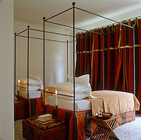 A pair of four-poster cast-iron beds, designed by Mimmi O' Connell, dominates this twin bedroom