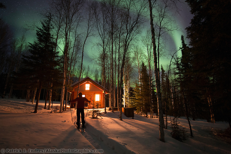 Man watches aurora borealis in a boreal forest in Fairbanks, Alaska.