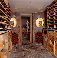 An impressive wine cellar lined with storage for wine botttles and a pair of Roman-style stone busts in the circular alcoves by the doorway