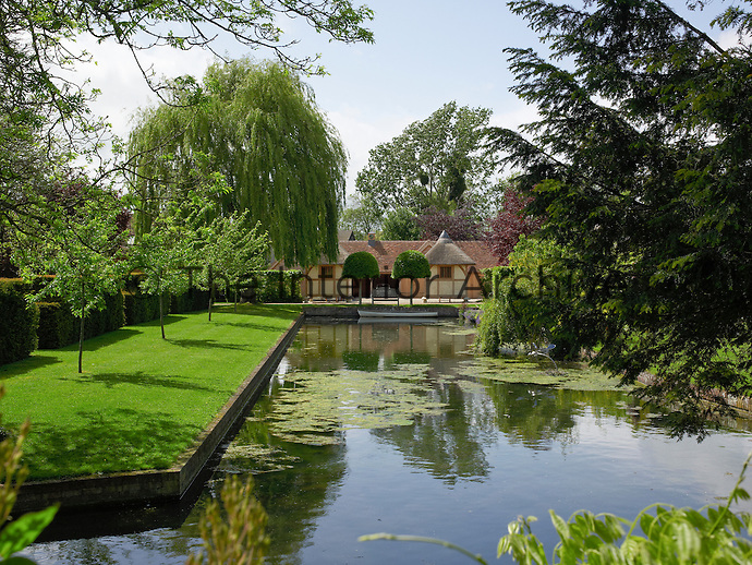 The water feature leading to the manor house elongates the view and focuses the gaze on the house at the bottom of the garden