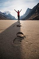 Female hiker lifts arms towards sun on empty Horseid beach, Moskenesøy, Lofoten Islands, Norway