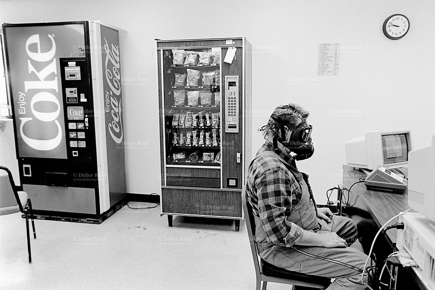 Usa. Utah. Tooele county. Deseret chemical depot. A worker is testing the gas mask's efficiency. Coca Cola soft drinks and food selling distributor's machine. Tooele chemical agent disposal facility (TOCDF). Program for destruction of chemical weapons and agent. Incinerating plant. Deseret chemical depot is distant 100 km from Salt Lake City. The Deseret Chemical Depot is one of eight Army installations in the U.S. that currently store chemical weapons. The weapons originally stored at the depot consisted of various munitions and ton containers, containing GB and VX nerve agents or H, HD, and HT blister agent. The Tooele Chemical Agent Disposal Facility is designed for the sole purpose of destroying the chemical weapons stockpile located at the depot. © 1998 Didier Ruef