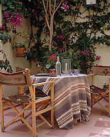 Old kilims are recycled in this courtyard with directors' chairs covered with strips of an old Moroccan kilim and a Greek rug used as a table cloth