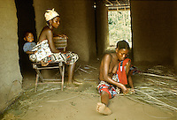 village life in Africa: Women of Kpelle tribe socializing inside hut, young one at right weaving mat, woman at left carrying baby strapped on her back, Liberia, West Africa.