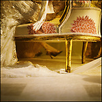 An elegant woman sitting on a gilded piece of furniture
