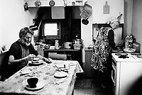 Switzerland. Canton Graubunden. Bondo. Bregaglia valley. Breakfast for the Salis family. The husband is seated while his wife is preparing the food. Kitchen. Swiss alpine farmers. Alps mountains peasants.  © 1997 Didier Ruef