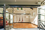 WIth sliding doors open wide and light streaming in, gymnastics equipment awaits in the open space of this play pavailion.