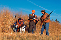 Three hunters with a dog take a coffee break.