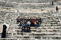 Jordan. Amman. Downtown. Town center. Antique roman open-air theatre. Ancien monument. Jordanian schoolboys and schoolgirls on a day visit accompanied by their women teachers who wear long dresses and a veil on their head as part of muslim tradition and religion. The class sits on the stone staircase and eats some junk food ( potato crisps, chips, sndwich). One of the three teachers walks down the stairs.  © 2002 Didier Ruef