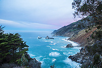 Sunrise on the Big Sur Coast where steep jagged mountains reach the rocky shore, lit up by a stormy sky