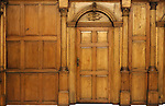 Wooden paneled wall and an arched door Victorian architecture style interior