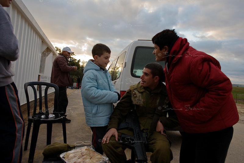 Kefar Azza, Israel, Jan 02, 2009.Israeli Paratroopers come back at dusk from a drill less than 2km from Gaza's border. Dror, 20, receives a surprise visit from his parents and younger brothers who brought him a Shabat supper. After several weeks of total closure, Israel has launched its most important military operation ever in the Gaza strip, following Hamas' refusal to extend the 6 months truce.