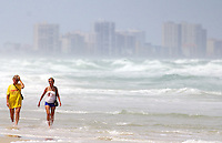 Two women walk on the beach with the heavy surf generated by Hurricane Irene and the Daytona Beach skyline in the background,  Ponce Inlet, FL, Thursday, August 25, 2011.   (Photo by Brian Cleary/www.bcpix.com)