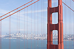 San Francisco, California; a view of the San Francisco skyline, viewed through the suspension wires of the Golden Gate Bridge in late afternoon