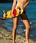 Closeup of legs of a young woman in bikini with a skateboard on the beach