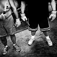 Two men hold dull knives which are used in some of the fights on fight nights. 'Gentlemen's Fight Clubs' are held in private garages or homes. People who work as software engineers and programmers during the day meet there to fight. This way they are able to let out their tensions, frustrations and passions in somtimes overtly violent ways. The participants are known to use keyboards, dustbusters and rolled up women's magazines in their fights. Silicon Valley, California.