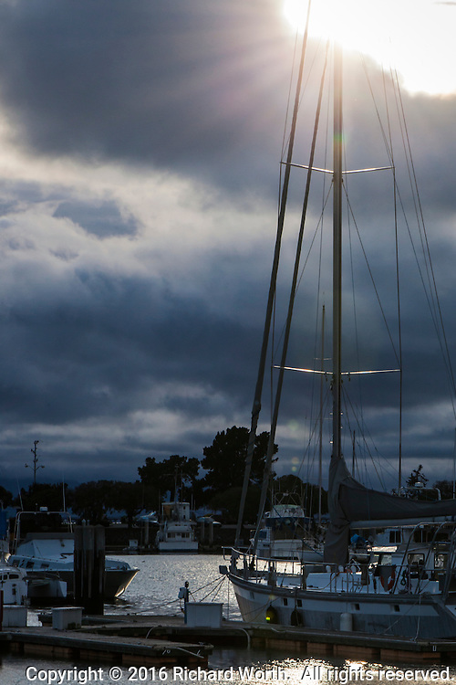 Through a break in the clouds, the sun shines down on boats moored at San Leandro Marina, on San Francisco Bay.