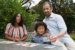 Berkeley CA Mixed race couple, African American and white playing lotto game with son, five  MR
