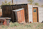 Wooden outhouse behind shack in rural Nev.