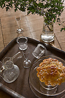 A metal tray with a few antique glasses and a freshly baked cake is placed on the rustic table top in the kitchen