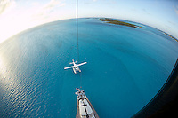 Exumas, Bahamas 2006 - Mast top view of 115 foot Sloop 'Tenacous'  and a Cessna Caravan seaplane tied to the stern in the shallow waters off the Exumas chain of islands in the Bahamas.