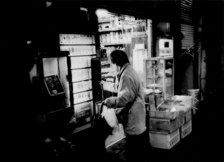 "Customer buys canned drink from a vending machine in front of a typical family-run shop on a ""shoutengai"" shopping street in Tokyo have been decreasing in number as their financial viability have decreased and owners have aged.  If times were not hard enough, the recent economic crisis has come down hardest on such shops where the profit margin is most fragile, Taito Ku, Tokyo, Japan."