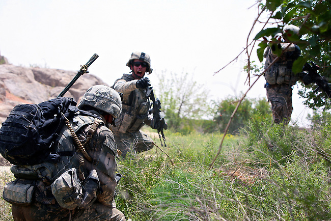 Staff Sgt. Dylan Lugibihl, 24, of Napoleon, Ohio, a squad leader with Company A, 2nd Battalion, 2nd Infantry Regiment yells for other soldiers to get on line and return fire after their patrol is attacked near the village of Zangabad in Panjwayi district, Kandahar province, Afghanistan. April 27, 2009. DREW BROWN/STARS AND STRIPES