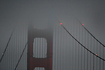 Fog surrounds the south tower of the Golden Gate Bridge just before dawn in San Francisco, California.