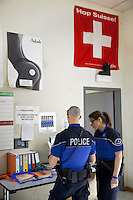 Switzerland. Geneva. Paquis police station. Two police officers check on a computer the identities of men who haver been earlier arrested. A swiss flag and a poster for Aubade lingerie ( a beautiful naked woman with a sexy underwear ) are on the wall. A policeman's shoe is placed on a lamp above the door. A police station or station house is a building which serves police officers and contains offices, locker rooms, temporary holding cells and interview/interrogation rooms. Both policemen are wearing a ballistic vest, bulletproof vest or bullet-resistant vest which is an item of personal armor that helps absorb the impact from knives, firearm-fired projectiles and shrapnel from explosions, and is worn on the torso. Soft vests are made from many layers of woven or laminated fibers and can be capable of protecting the wearer from small-caliber handgun and shotgun projectiles, and small fragments from explosives such as hand grenades. The flag of Switzerland consists of a red flag with a white cross (a bold, equilateral cross) in the centre. It is a sovereign-state flag. 15.05.12 &copy; 2012 Didier Ruef