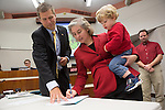 Satterlee signs paperwork for during her swearing-in ceremony.  Her son watches on on the procedure.