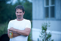 Man with a goatee holding a beer outdoors