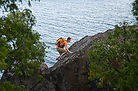 A young man rock climbs on cliffs overlooking Lake Superior in Marquette Michigan.