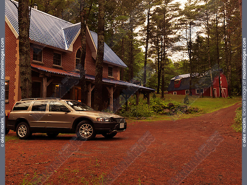 Brick country house or cottage and Volvo XC70 station wagon car in Muskoka, Ontario, Canada countryside scenery.