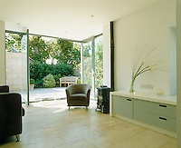 Plate glass windows open out onto a patio garden from this contemporary extension which is heated by a small enamelled stove