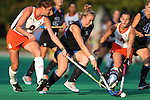 19 September 2014: Duke's Heather Morris (center) is defended by Virginia's Tara Vittese (8) and Maddie DeCerbo (4). The Duke University Blue Devils hosted the University of Virginia Cavaliers at Jack Katz Stadium in Durham, North Carolina in a 2014 NCAA Division I Field Hockey match. Virginia won the game 2-1.