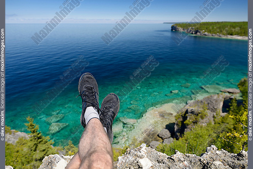 Legs of a person sitting on a cliff of Georgian Bay, lake Huron at Bruce Peninsula National Park, Ontario, Canada