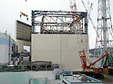 September 20, 2011, Okumamachi, Japan - A crane hoists a side panel as construction works continue to cover up the heavily damaged Unit 1 reactor of Fukushima No. 1 nuclear power plant in Okumamachi, Fukushima Prefecture, some 210km northeast of Tokyo, on Thursday, September 15, 2011. Tokyo Electric Power Co., the troubled plant operator known as TEPCO, has started the project in covering up the No. 1 reactor building with polyester sheets in a bid to prevent the dispersal of radioactive substances into the air. The roughly one-millimeter-thick sheets will be attached to the steel frames of the 54-meter-high building. To minimize workers' exposure to radiation, the 140-meter-tall crane designed to ward off radiation will set up 62 pre-assembled parts at the reactor in the operation TEPCO hopes to be completed by September. The Photo was released in Tokyo on September 17. (Photo by TEPCO/AFLO) [0006] -mis-