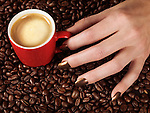 Closeup of woman's hand with a cup of coffe latte on coffee beans
