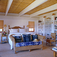 The ceiling of the bedroom is lined with bamboo and the bed, sidetable and sofa are of cane