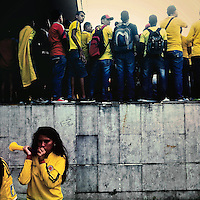 A Colombian girl plays a trumpet while watching the football match between Colombia and Uruguay at the FIFA World Cup 2014, in a park in Cali, Colombia, 28 June 2014.