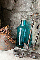 An alcove in the stone wall displays a collection of antique keys and other objects