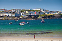 Ocean front houses and child playing on sandy beach at Kilkee  County Clare, West Coast of Ireland