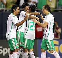 Mexico's Carlos Vela (11, second from left) gets a hug from teammate Efrain Juarez after Vela converted his penalty kick to clinch to give Mexico the victory.  Mexico defeated Costa Rica 2-1 on penalty kicks in the semifinals of the Gold Cup at Soldier Field in Chicago, IL on July 23, 2009.