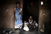28 year old Raju Haibro poses with his wife, Jima Haibro and two of his children for a photograph in his hut in Balighato village. He was shot on his left shoulder during a police shootout on January 6th 2006.